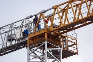 Парень в балаклаве выбрался на башенный кран в Минске и требует телевидение