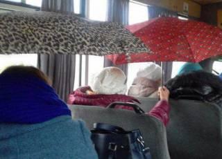 В киевской маршрутке пассажиры спасаются от дождя с помощью зонтов